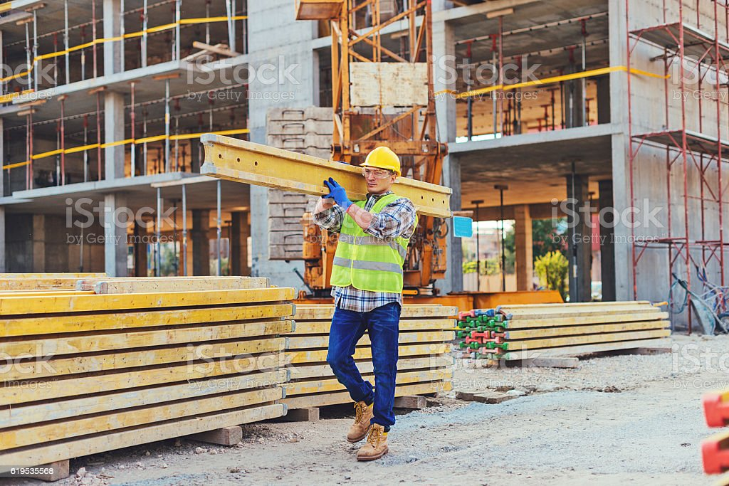 Construction worker carrying planks stock photo