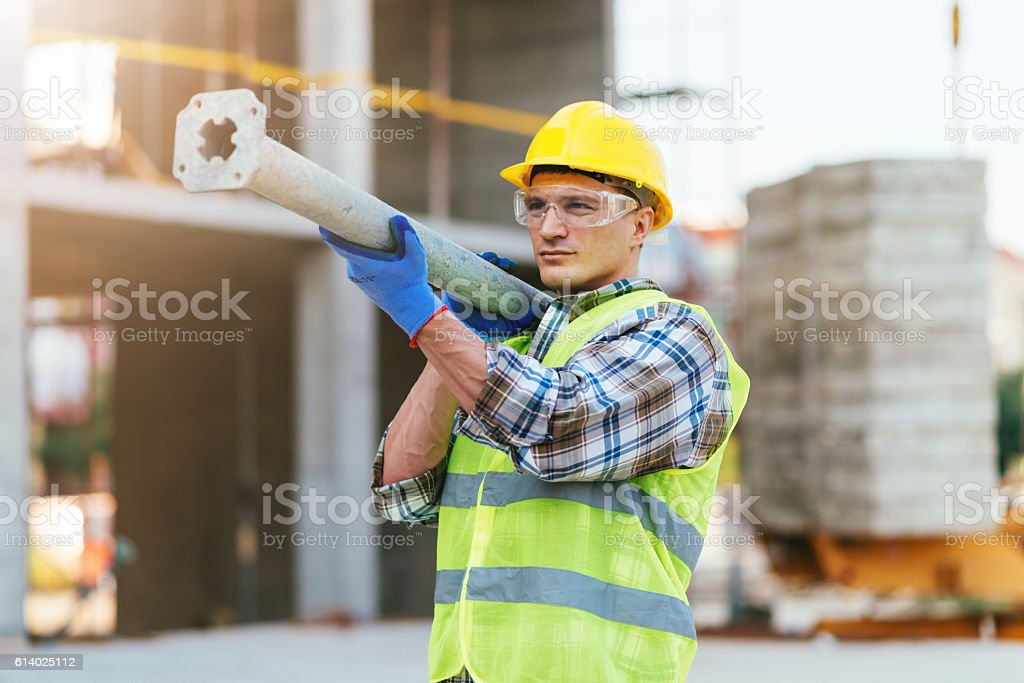 Construction worker carrying steel rod stock photo
