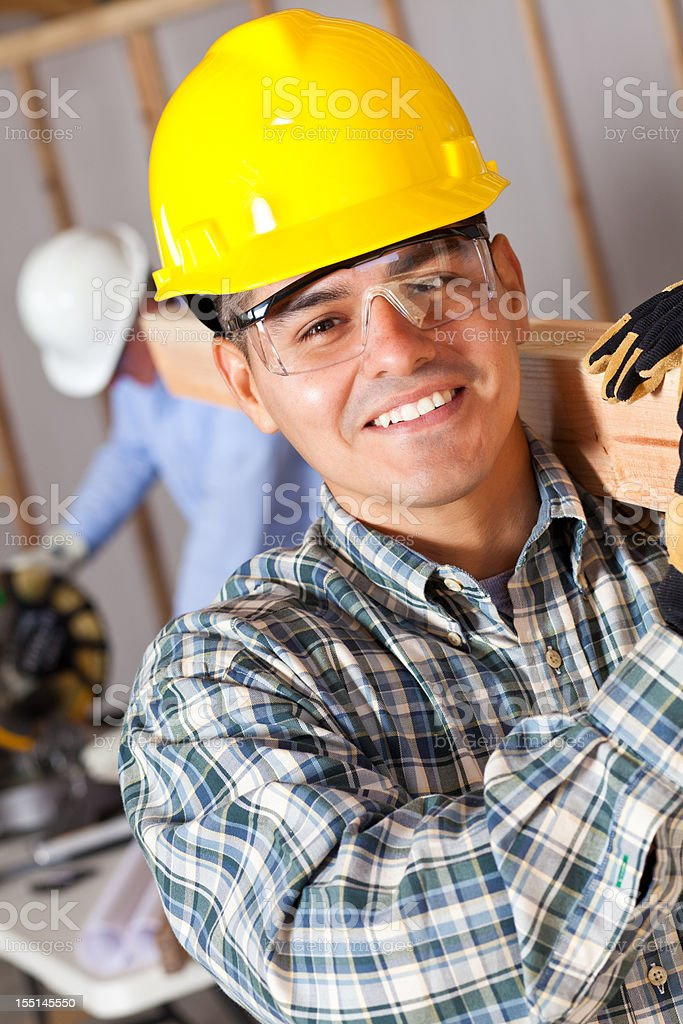 Construction worker carrying wood at work site royalty-free stock photo