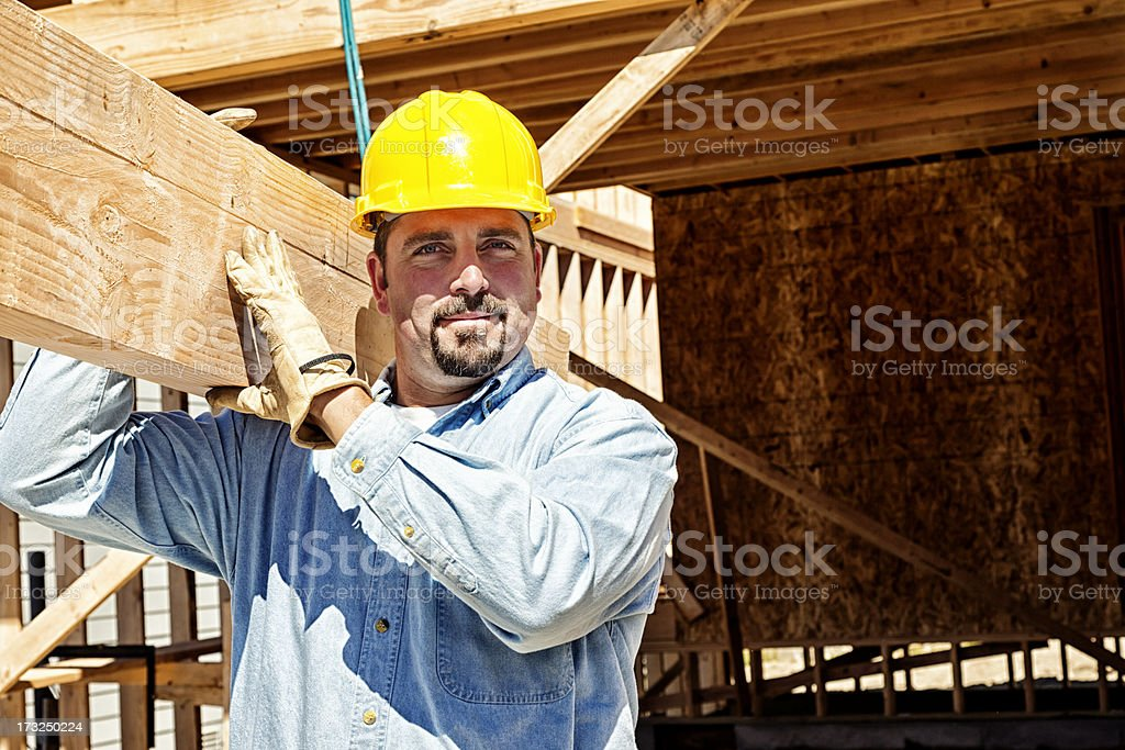 Construction Worker Carrying Wood Beam royalty-free stock photo