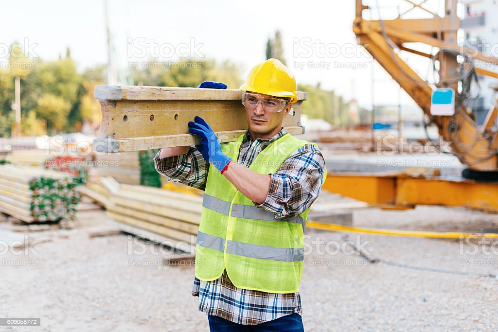 Construction worker carrying wooden plank for concrete support stock photo