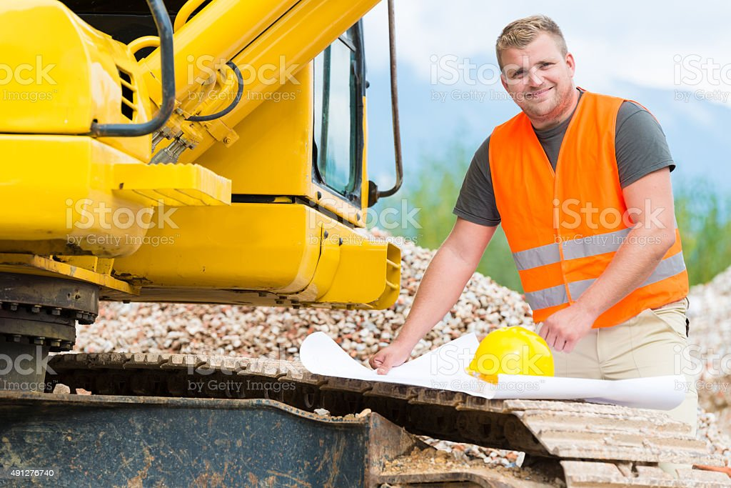 Construction worker checking blueprint stock photo