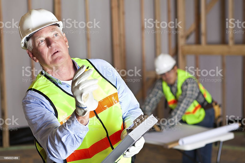 Construction worker checking list at a building site royalty-free stock photo