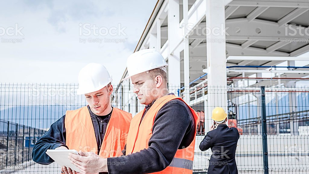 Construction worker checking plans stock photo