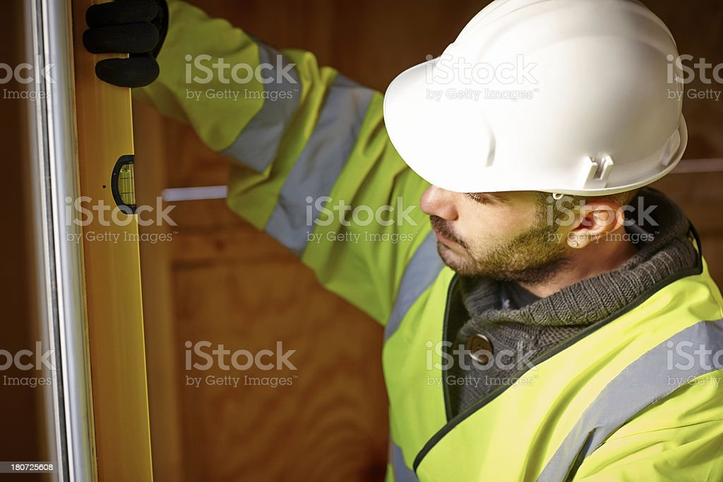 Construction worker checking the vertical level at site royalty-free stock photo