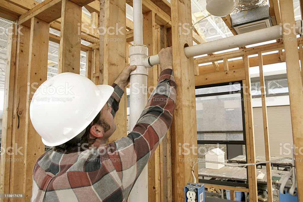 Construction Worker Connecting Pipe stock photo