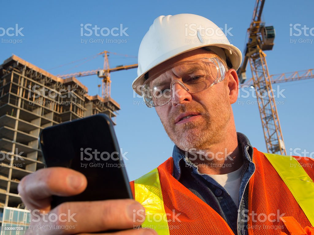 Construction Worker, Cranes, and Communication with Smart Phone stock photo