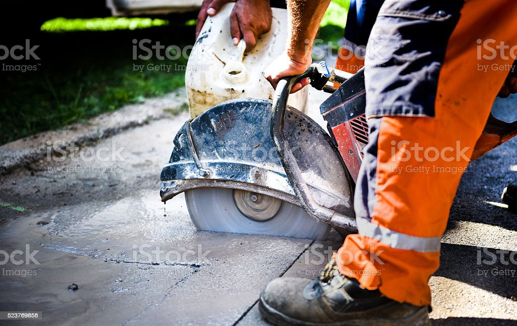 Construction worker cutting Asphalt paving for sidewalk stock photo