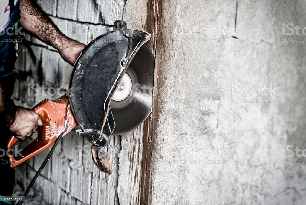 Construction Worker cutting wall with circular saw stock photo