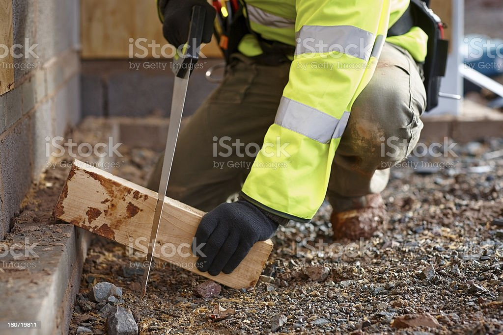 Construction worker cutting wooden plank with saw royalty-free stock photo