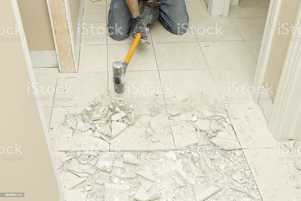 Construction Worker Demolishing Hallway Tile with Sledgehammer royalty-free stock photo
