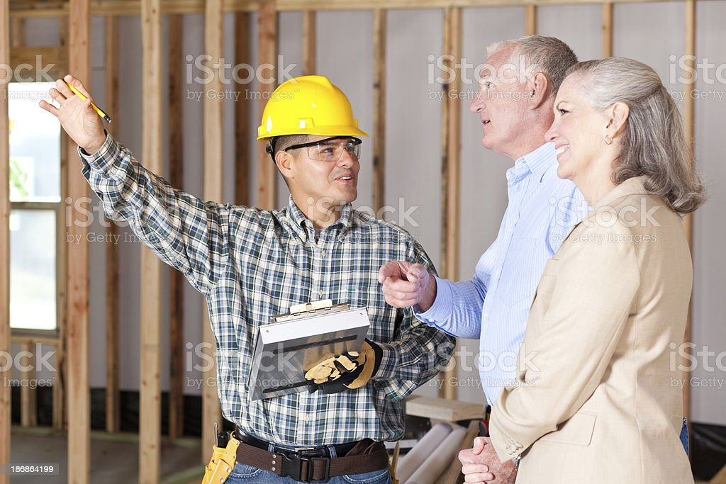 Construction worker discussing house building with home owners royalty-free stock photo