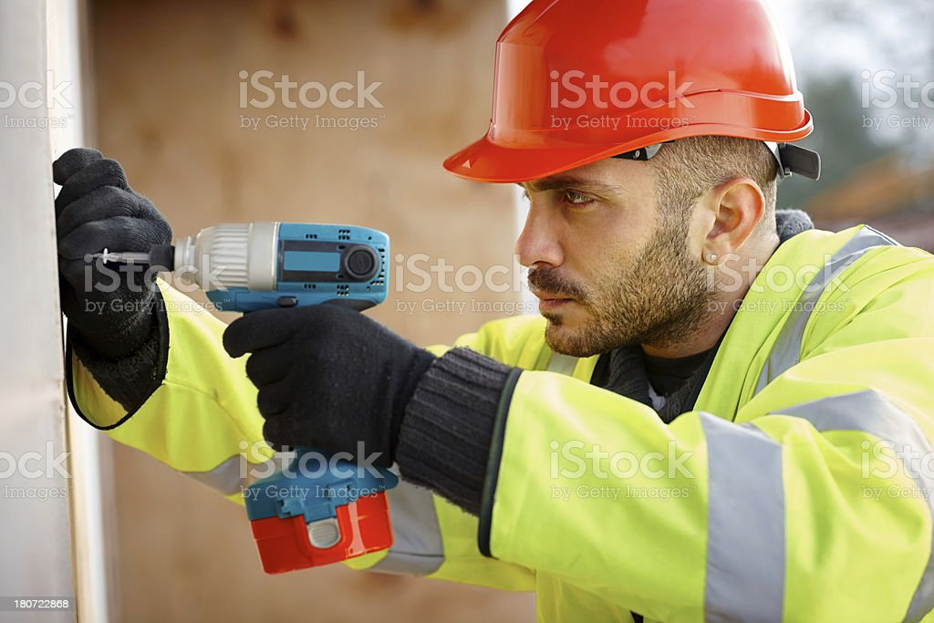 Construction worker drilling a screw in wall royalty-free stock photo