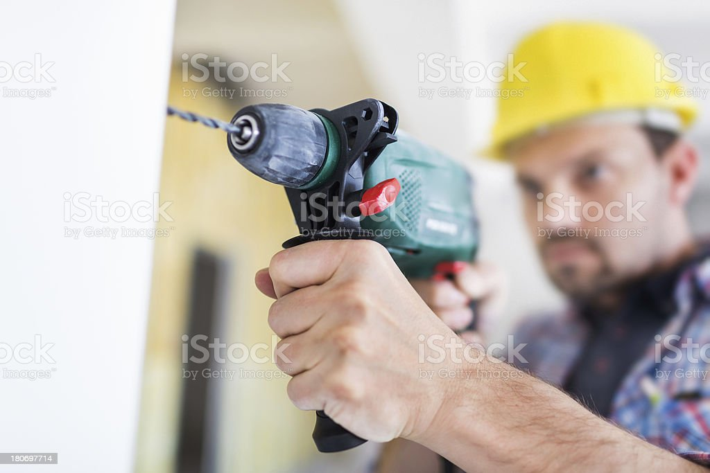 Construction Worker Drilling In Wall stock photo