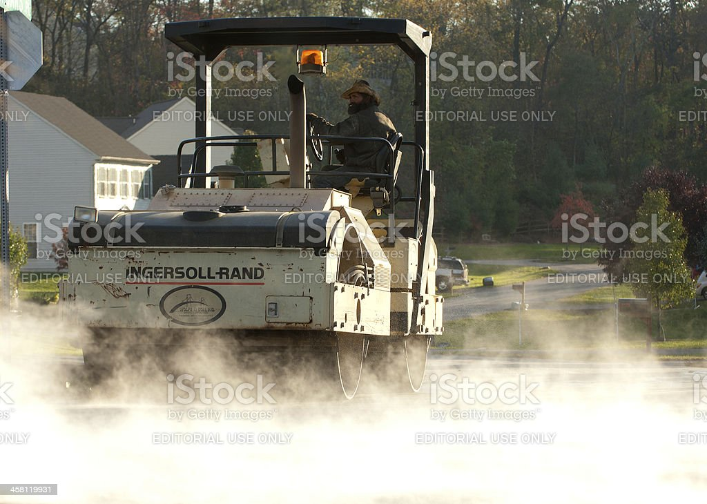 Construction worker drives a steam roller in neighborhood stock photo