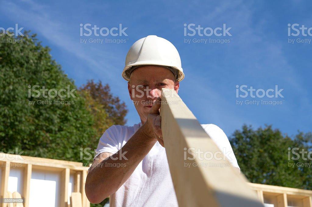 Construction Worker Examing Lumber stock photo