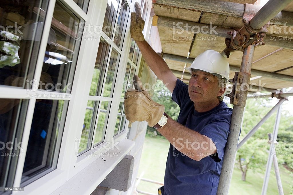 Construction Worker Fitting Double Glazed Window royalty-free stock photo