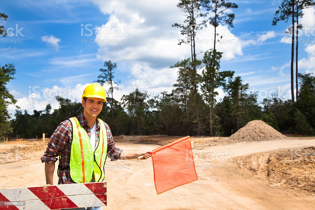 Construction worker, flagman directs traffic at job site. stock photo