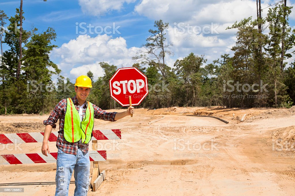 Construction worker, flagman holds stop sign at job site. stock photo