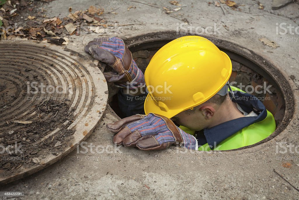 A construction worker going down a manhole stock photo