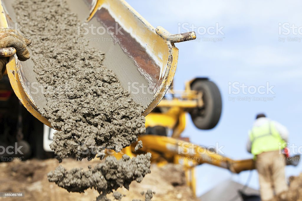Construction Worker Guiding Cement Mixer Truck Trough stock photo