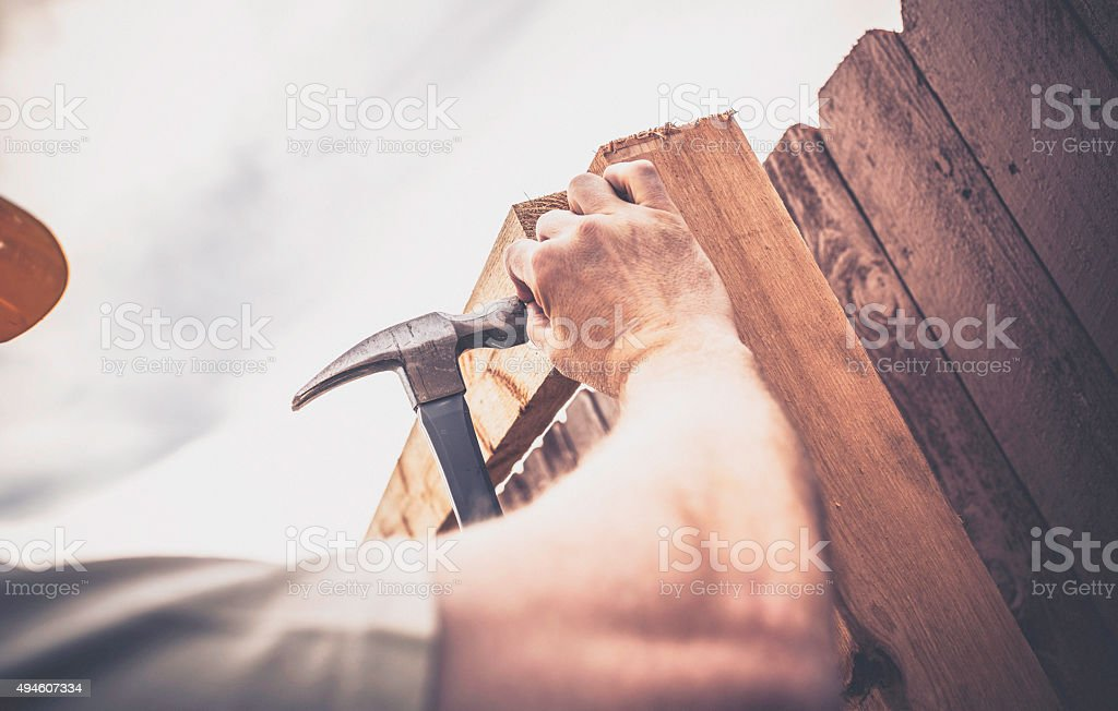 Construction worker hammering nail into fence framework. New construction. Fences. stock photo