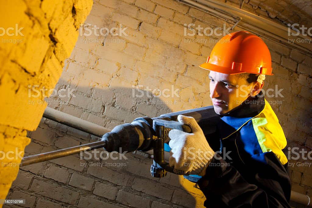 Construction worker hold perforator and drilling brick wall royalty-free stock photo