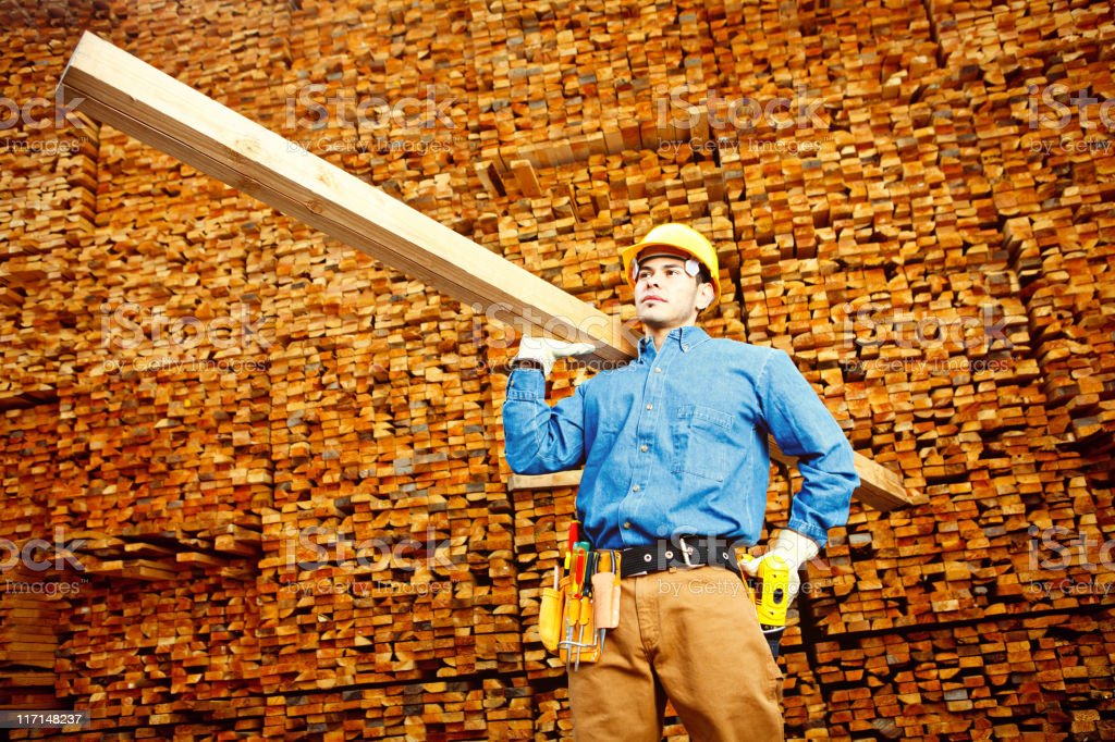 Construction worker holding beam against wood background royalty-free stock photo
