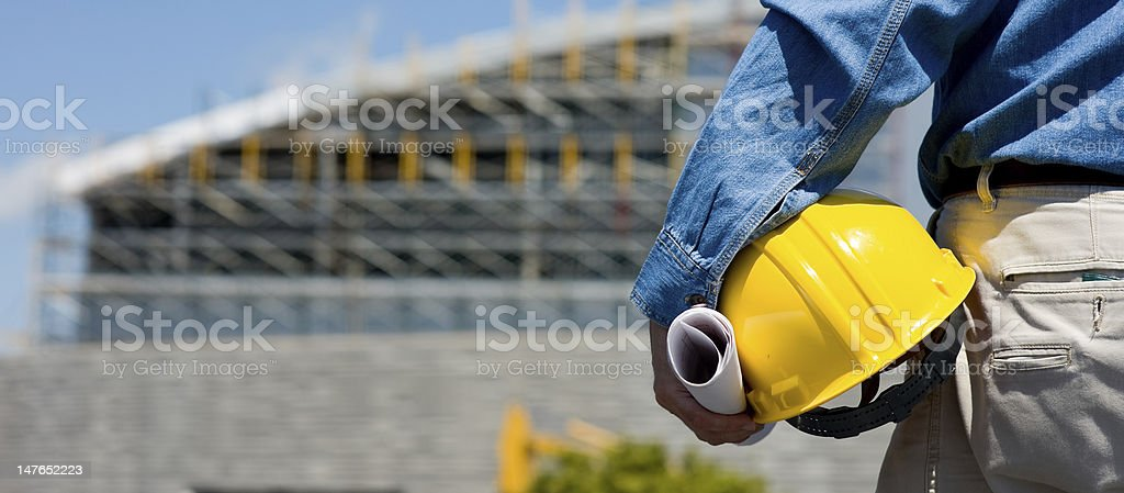 Construction worker holding hard hat stock photo