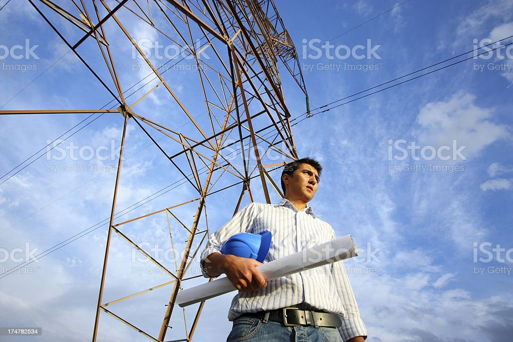 Construction worker holding hard hat under electrical tower stock photo