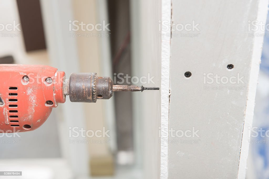 Construction worker holding the hand drill stock photo