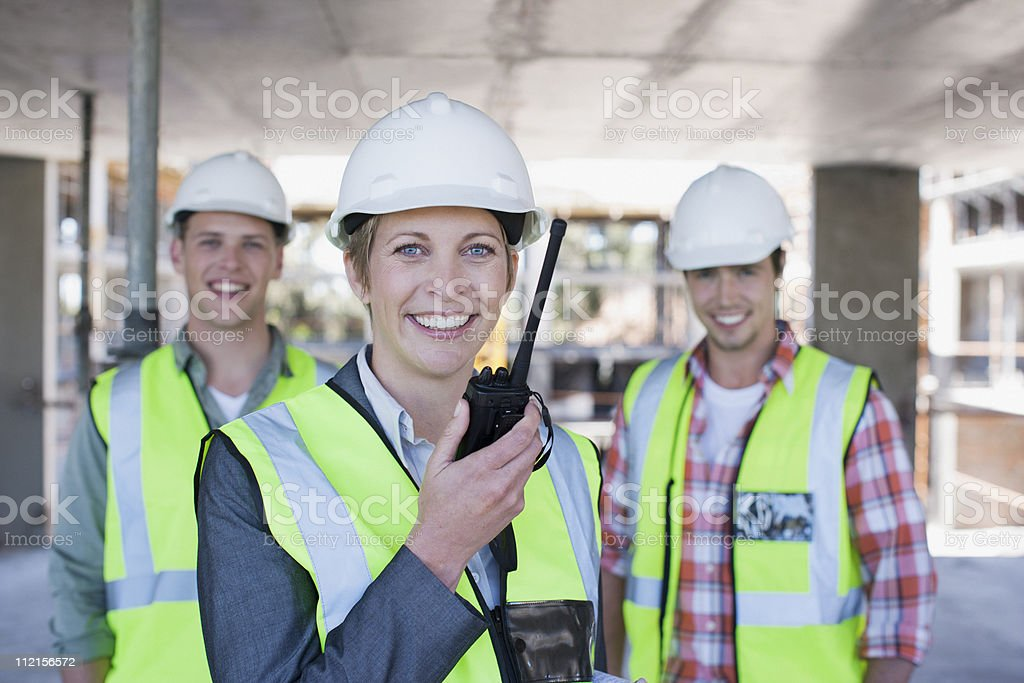 Construction worker holding walkie talkie on construction site stock photo