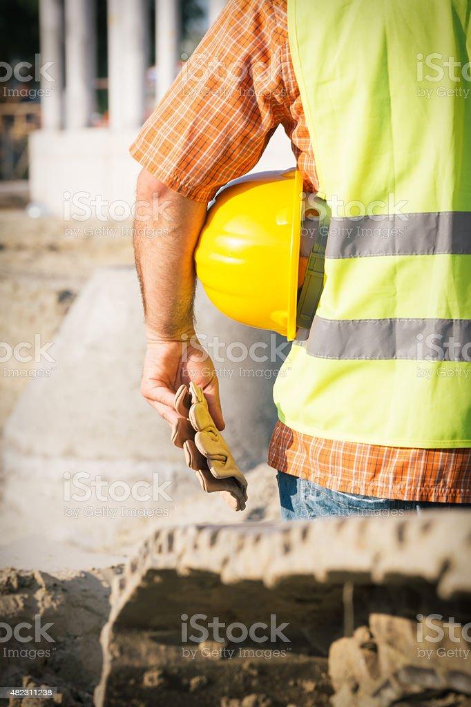 Construction worker holding yellow hardhat stock photo