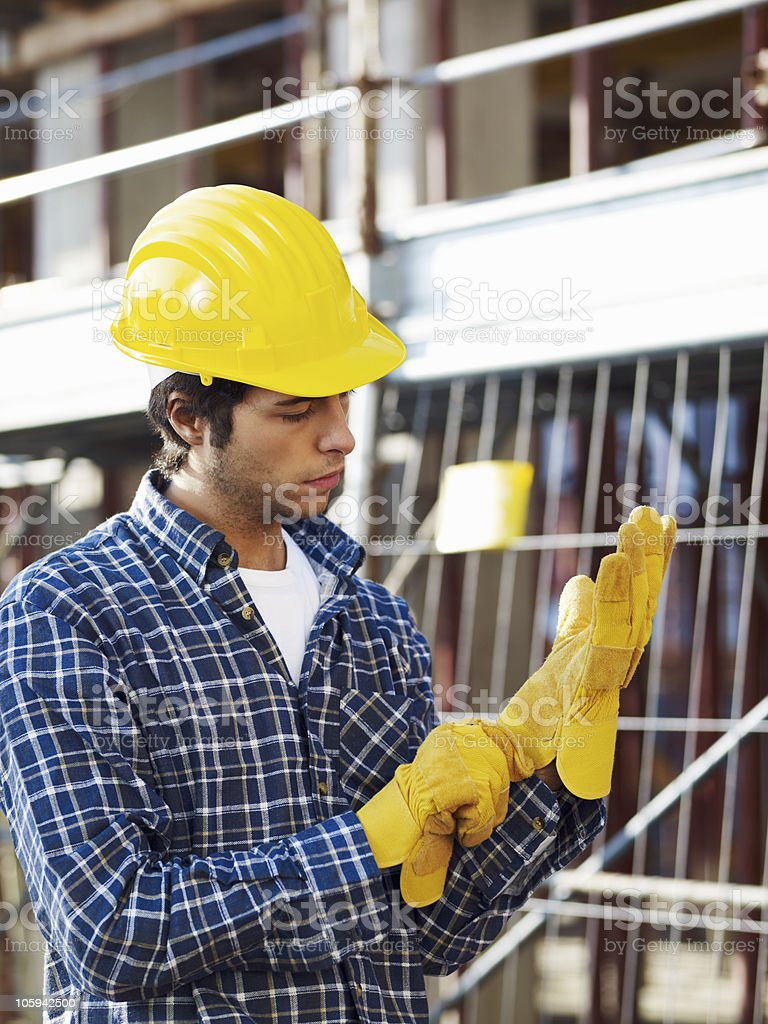 A construction worker in a helmet putting on gloves  stock photo