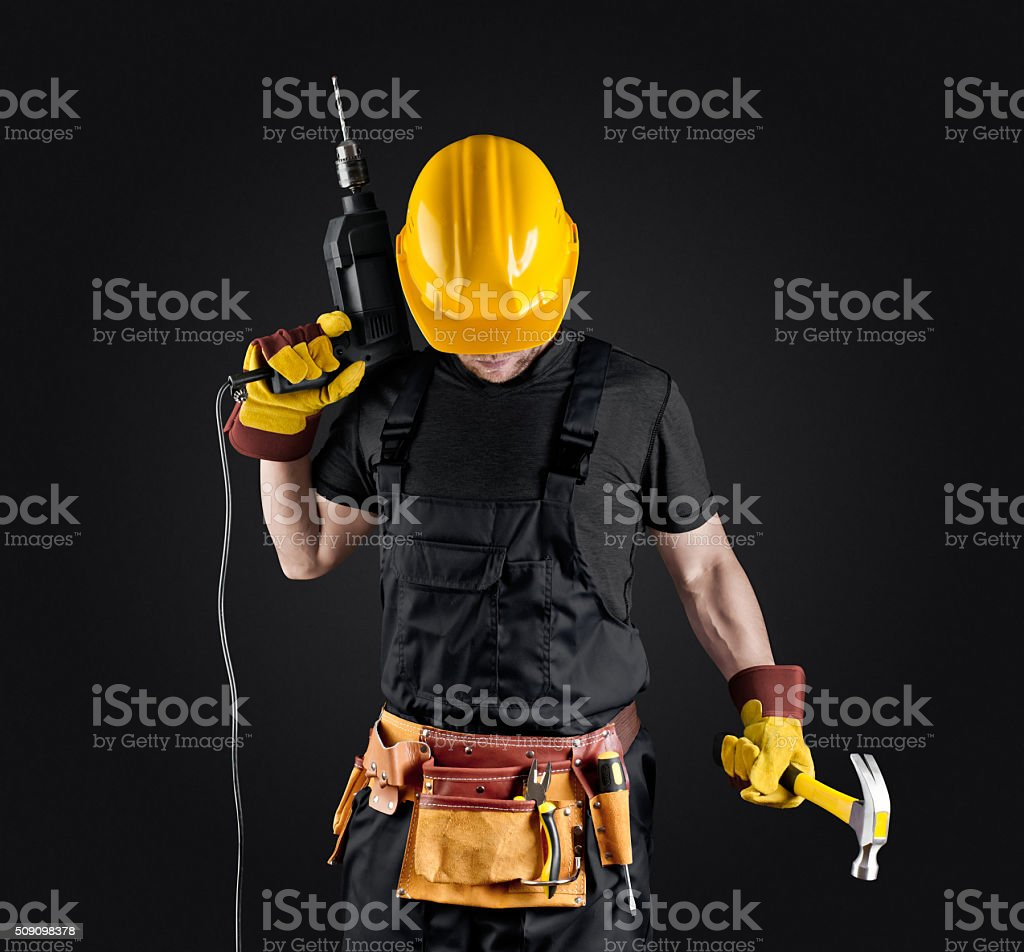 construction worker in helmet with hammer and drill stock photo
