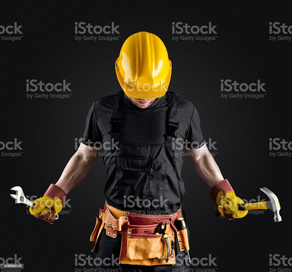construction worker in helmet with hammer and wrench stock photo