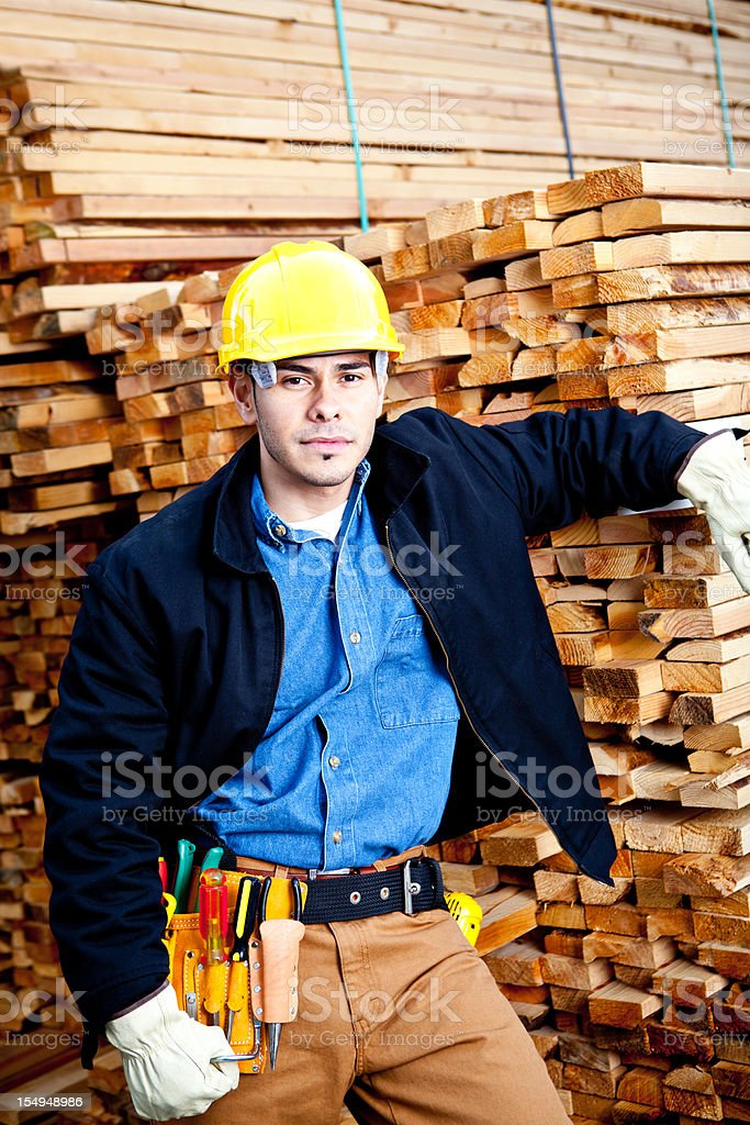 construction worker in jacket posing against lumber royalty-free stock photo