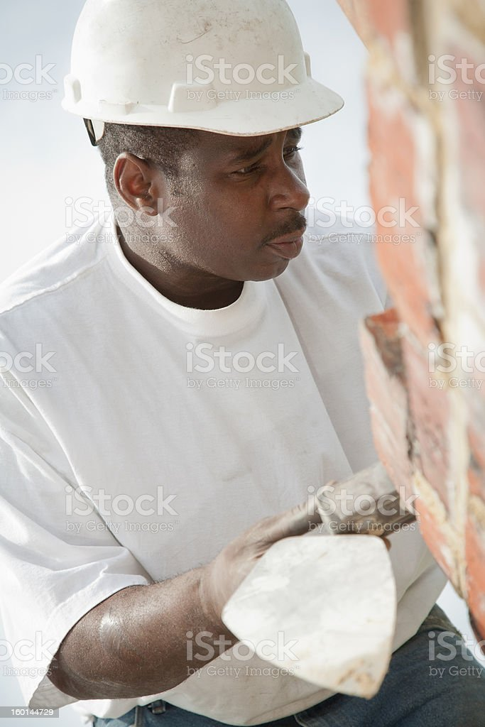 Construction worker inspects bricks. royalty-free stock photo