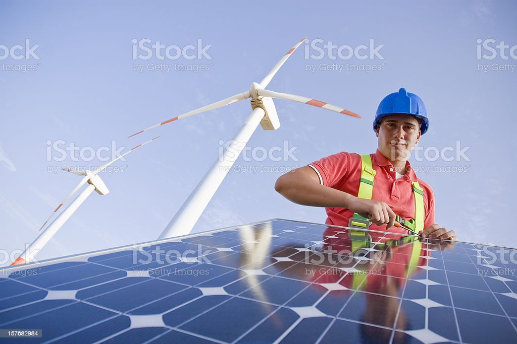 A construction worker installing a solar panel royalty-free stock photo