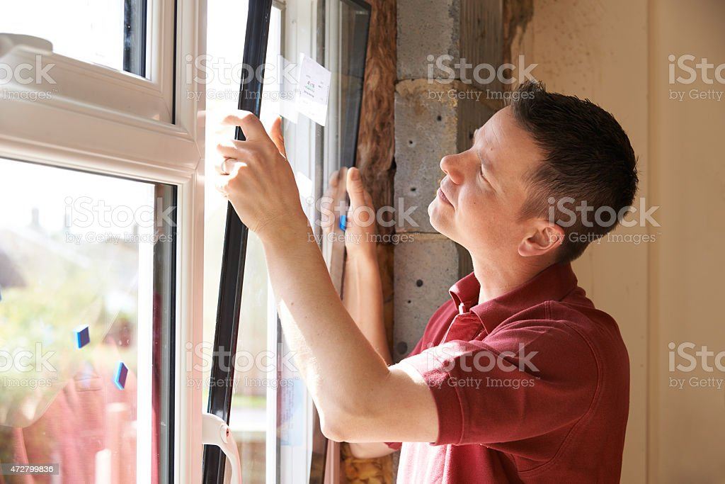 Construction Worker Installing New Windows In House stock photo