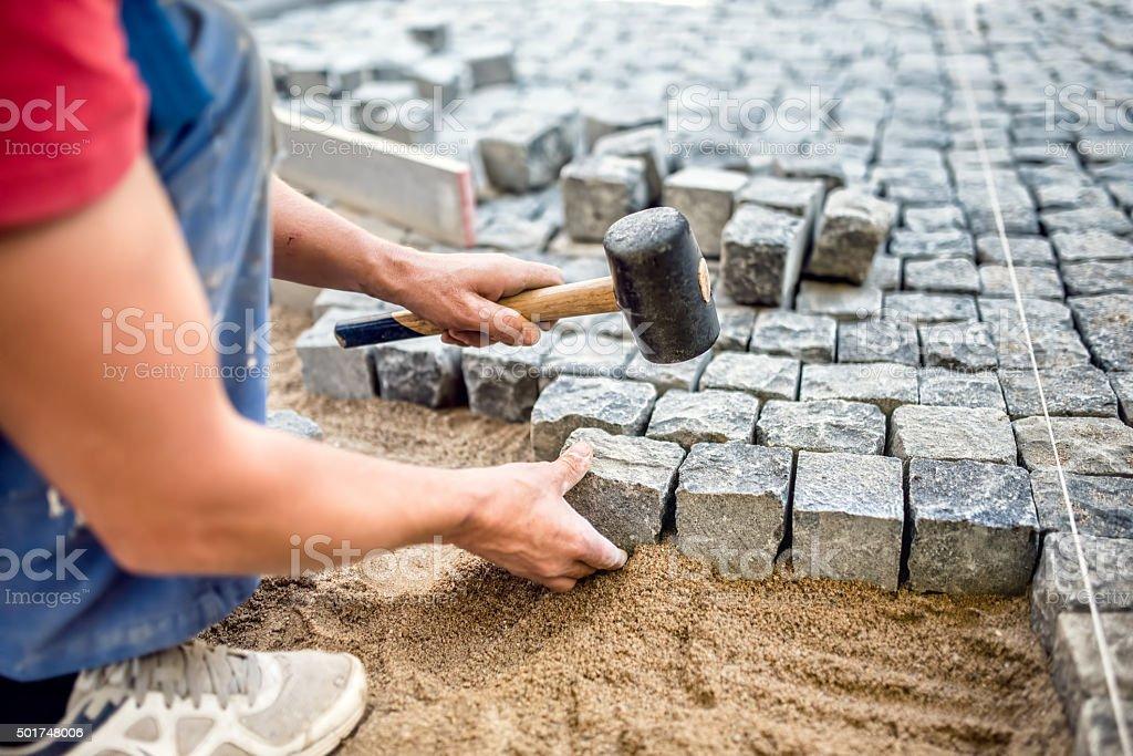 Construction worker installing stone blocks on pavement stock photo