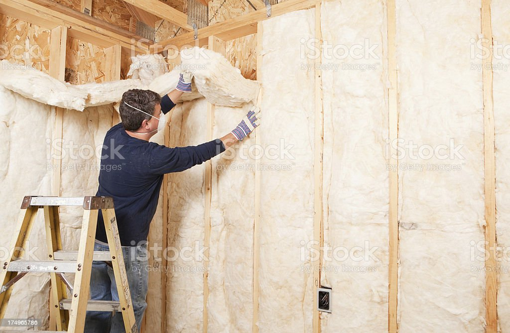 Construction Worker Insulating Wall with Fiberglass Batt stock photo