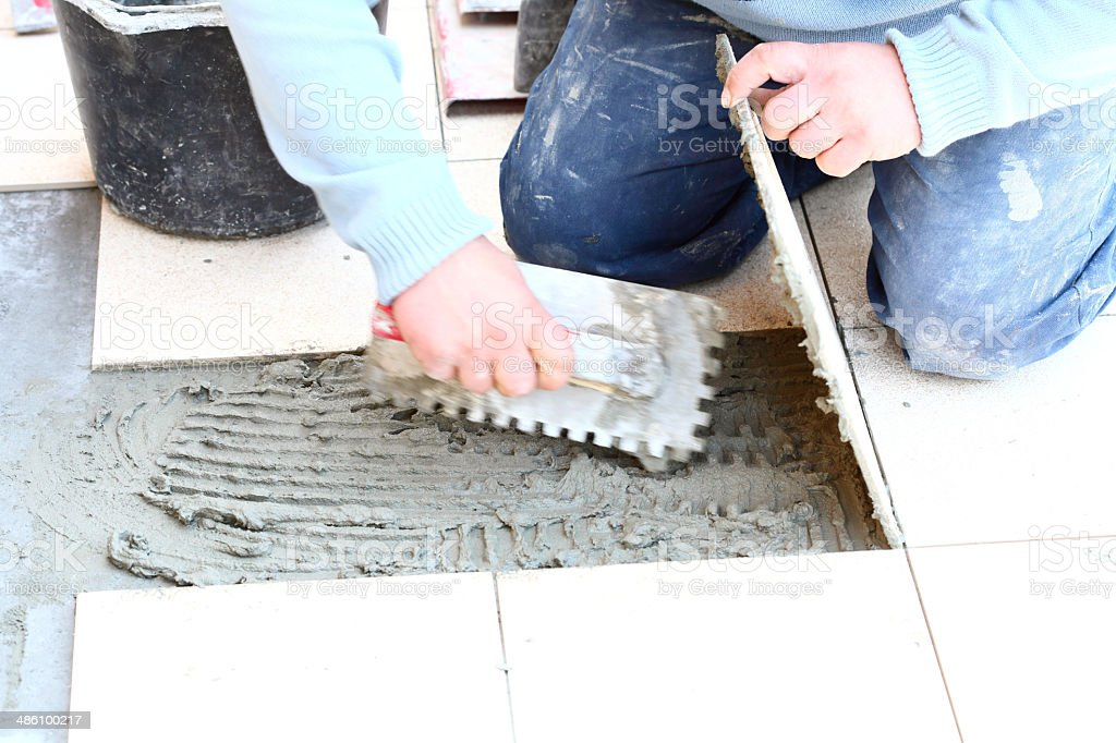 Construction worker is tiling at home royalty-free stock photo