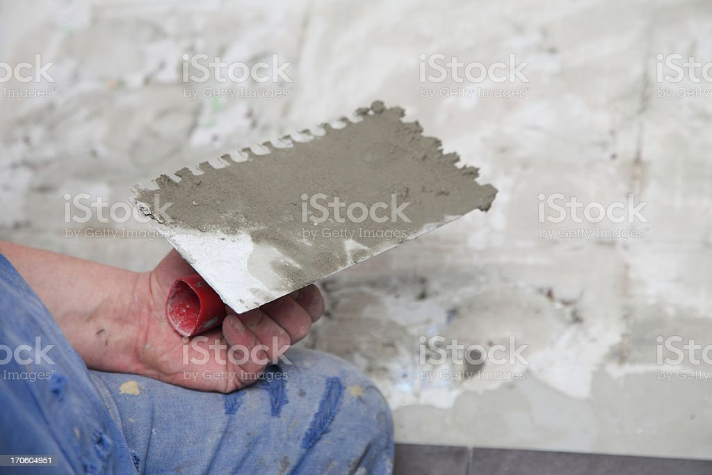 Construction worker is tiling at home tile floor adhesive royalty-free stock photo
