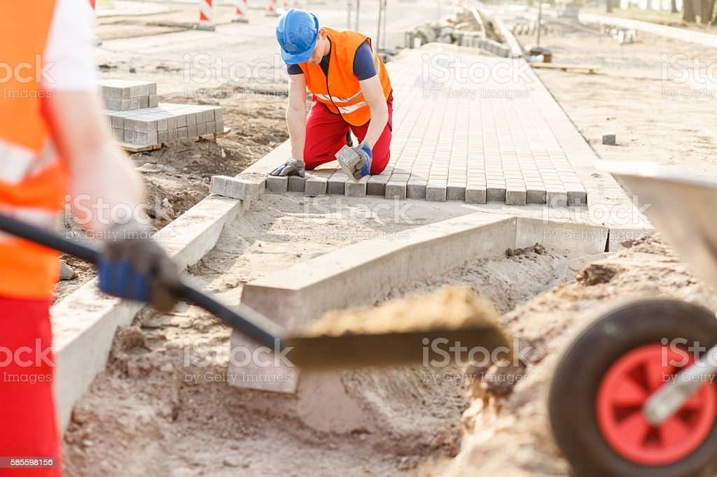 Construction worker laying cobblestones stock photo