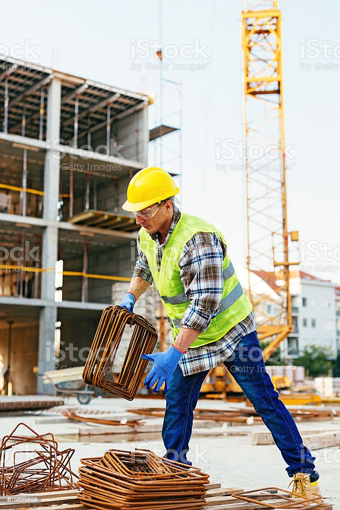 Construction worker lifting steel rods stock photo