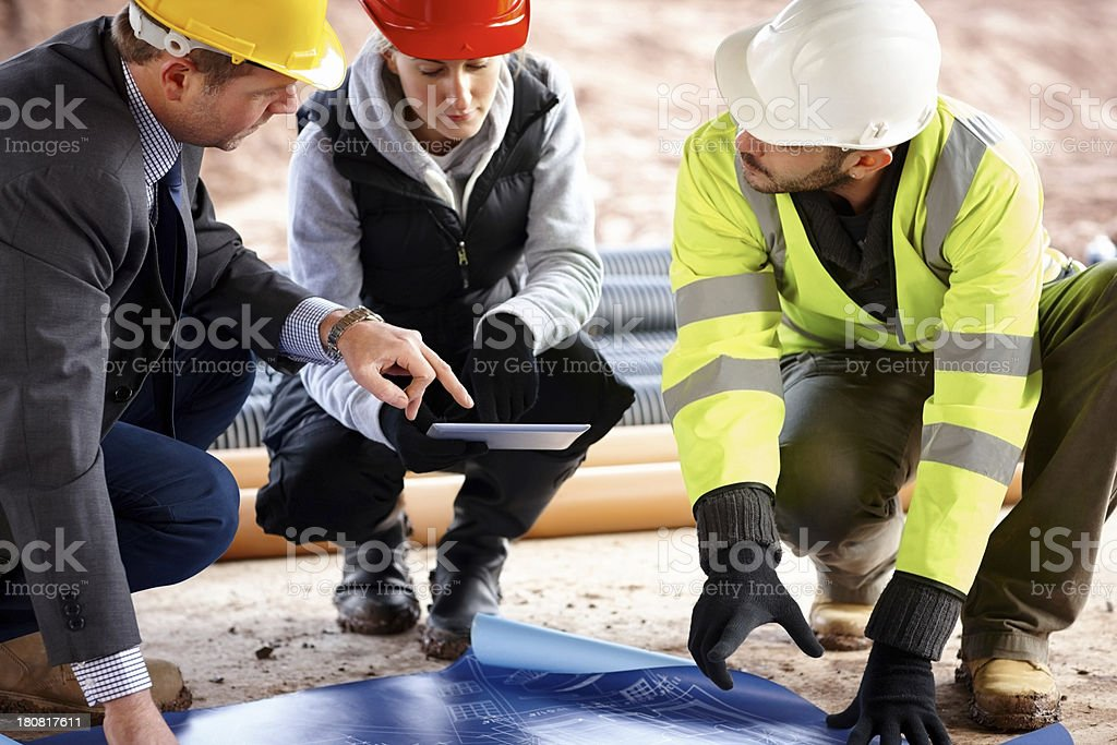Construction worker looking at blueprints royalty-free stock photo