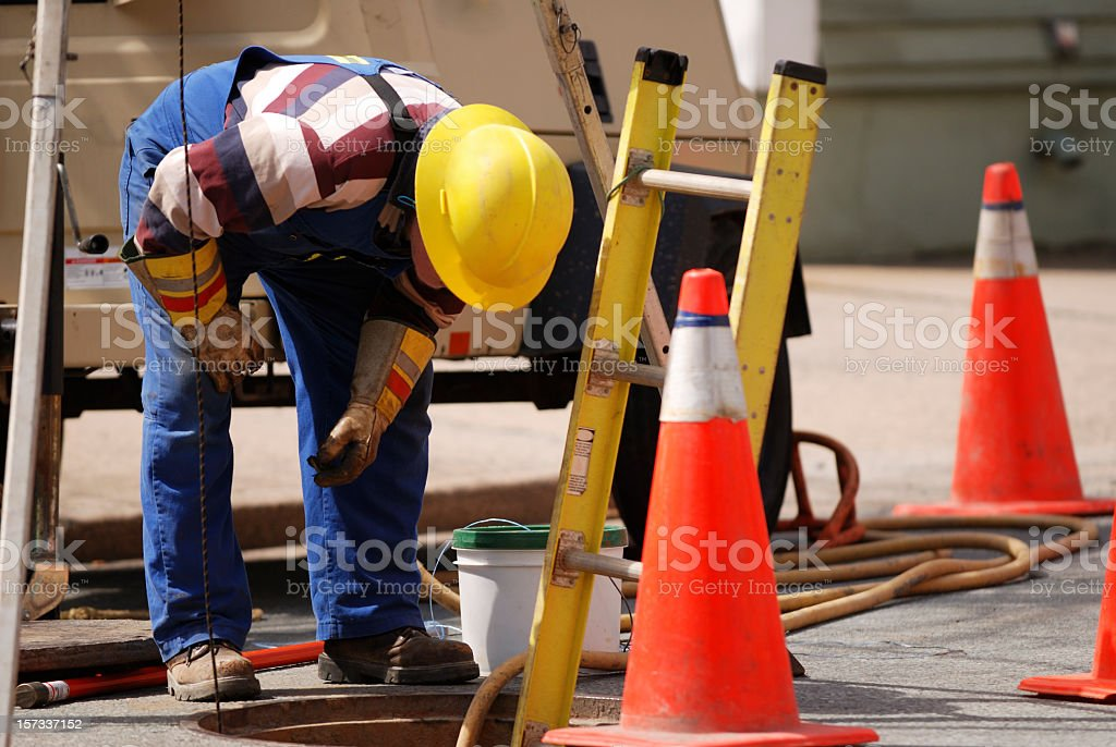 Construction Worker Looking Down man hole. stock photo