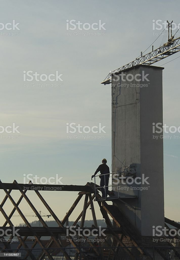 construction worker looks at the demolition of a building stock photo