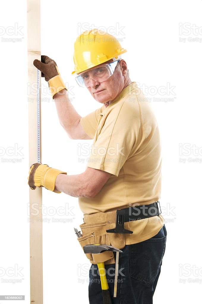 Construction worker measuring a piece of wood royalty-free stock photo